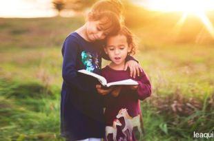 uma criança mais velha ensinando outra menor através de um livro que ambas seguram fazer o bem