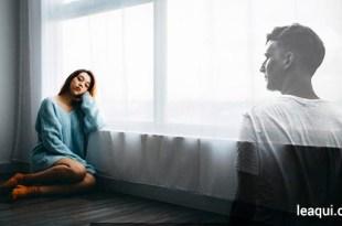 uma mulher sozinha com o braço apoiado em uma janela com ar de tristeza, enfrente a ela uma imagem de um rapaz transparente como se fosse um espírito relacionamentos depois da morte