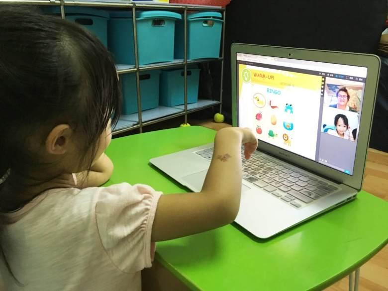 Zenny 老師帶著 Tanya 在臉譜上畫畫和玩 Bingo 遊戲,透過遊戲引發孩子的學習興趣。