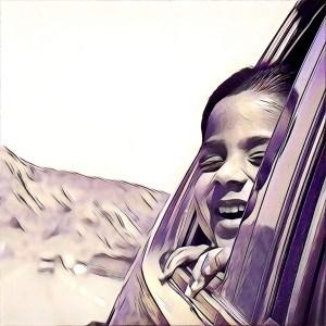 Niña viajando feliz en el asiento de atrás del coche