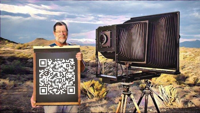 Hombre sosteniendo código QR junto a cámara de fotografía antigua