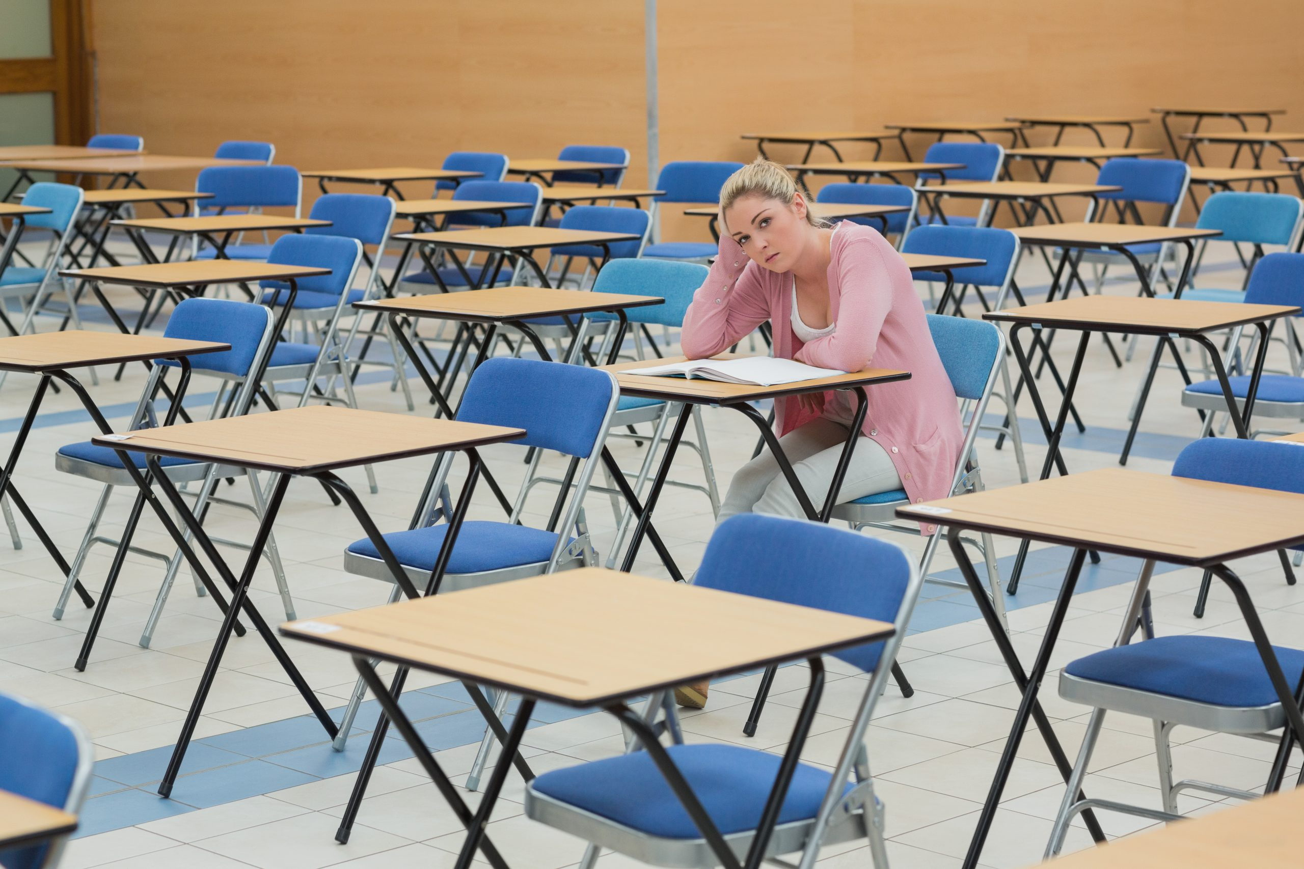 girl sitting alone in an exam hall