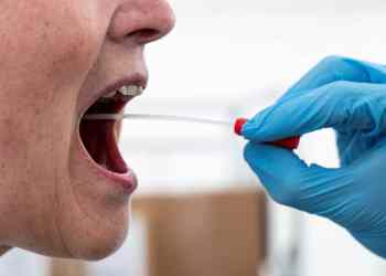 A medical worker performs a mouth swab on a patient to test for the coronavirus disease (COVID-19) in a new tent extension of Danish National Hospital Rigshospitalet in Copenhagen, Denmark April 2, 2020.  Ritzau Scanpix/Niels Christian Vilmann via REUTERS    ATTENTION EDITORS - THIS IMAGE WAS PROVIDED BY A THIRD PARTY. DENMARK OUT. NO COMMERCIAL OR EDITORIAL SALES IN DENMARK.