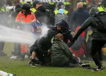 Police uses a water canon during a protest against restrictions put in place to curb the spread of the coronavirus disease (COVID-19), in Amsterdam, Netherlands January 24, 2021. REUTERS/Eva Plevier