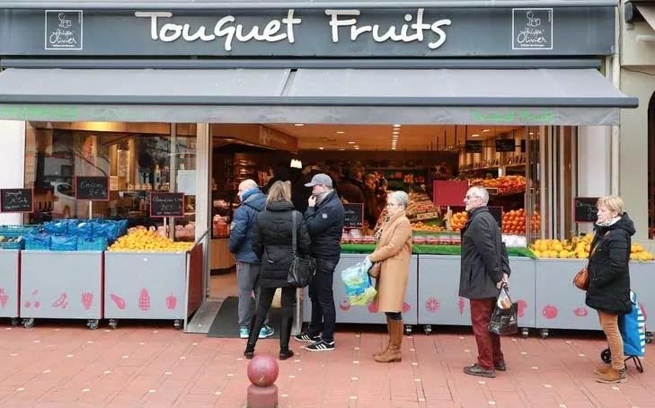 les consommateurs font la queue devant un petit commerce