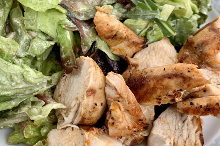 Gegrillte Hühnerbrust auf rotem Kopfsalat