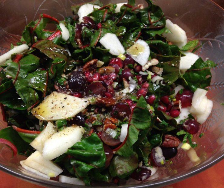 Mangold salat mit Birne, Granatapfelkernen, Trauben, Pekan Nüssen und Dattel Vinaigrette