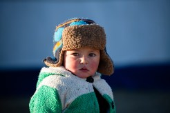 A kazakh kid walking along the steppes with her family