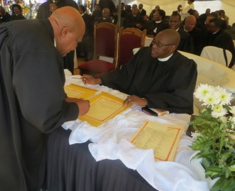 Ministers sign the ordination certificate