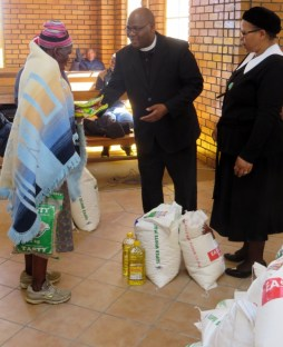 Rev. T. S. Masemene and Mrs. Mary Posholi hand out food parcels