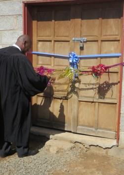 Rev. Masemene cuts the ribbon