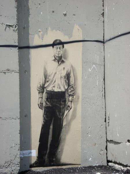 Una pintura con la imagen de Mahmoud Darwish en el muro del apartheid levantado por Israel.