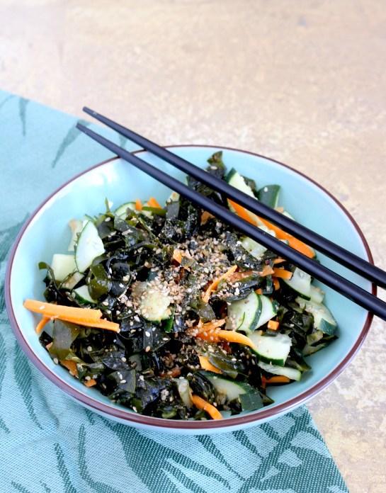 Assiette avec salade de wakamé, concombre, carottes, sésame et des baguettes