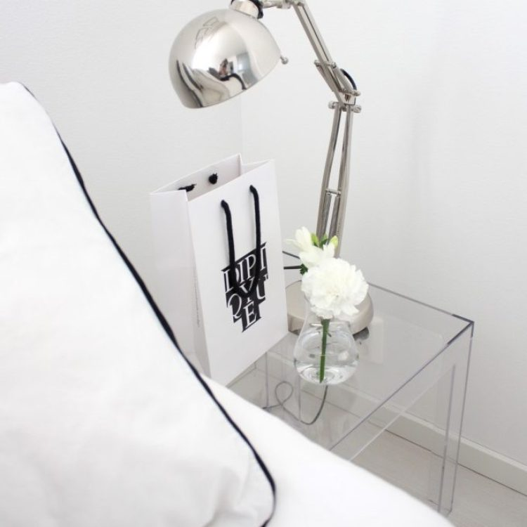 modern clear nightstand with bedroom table lamp.
