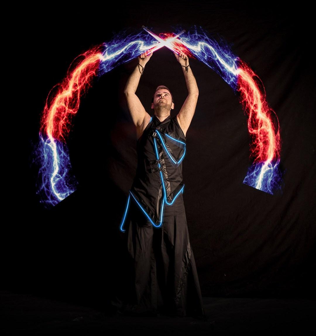 mężczyzna krzyżujący świecące pałki w rękach podczas pokazu światła