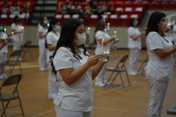 Female nursing graduates in white uniforms and masks holding symbolic lamps.