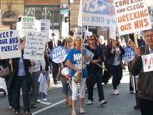 walking with others along the demonstration route alongside Keep Our NHS Public national banner
