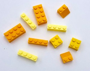 A pile of yellow LEGO bricks of subtlety different shades