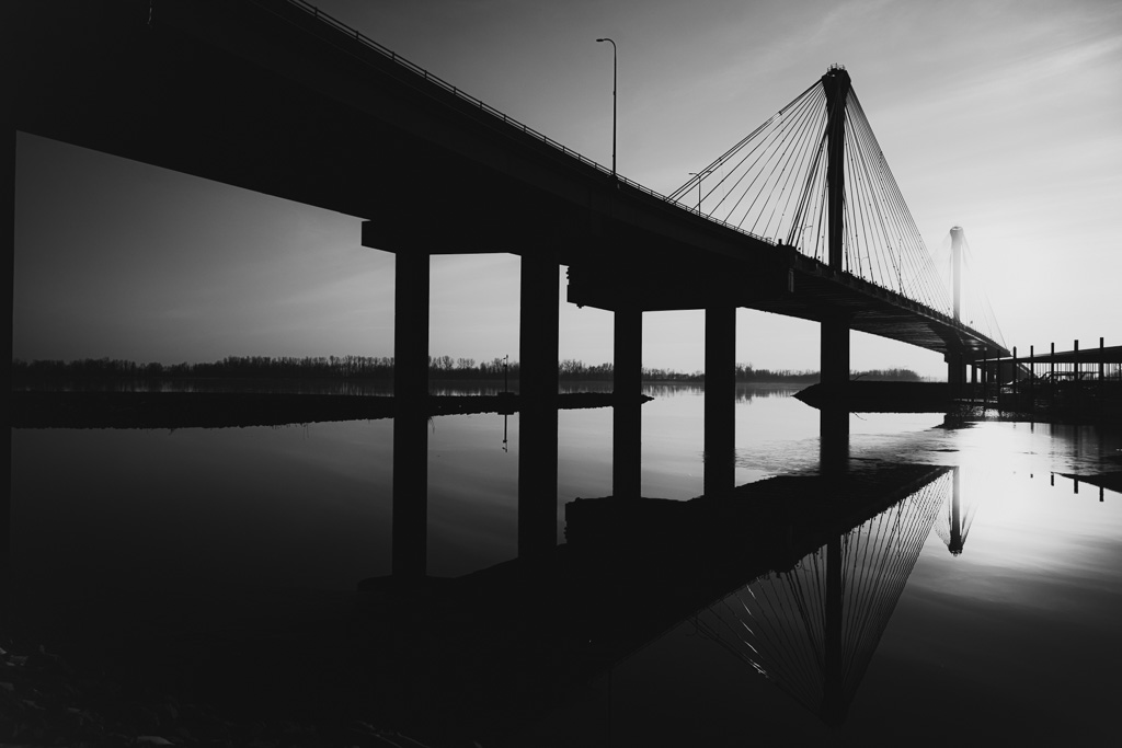 black and white fine art photography bridge and water reflection at sunset