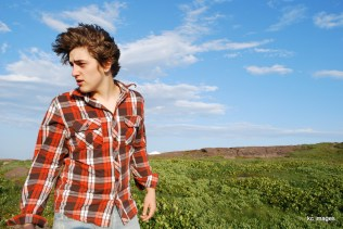 boy in orange plaid with blue sky background.