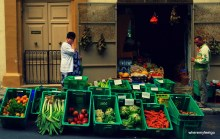 many green bins with vegetables of many colours in them. a woman in a blue dress and a white sweater is standing over the bins wih her hand on her mouth.