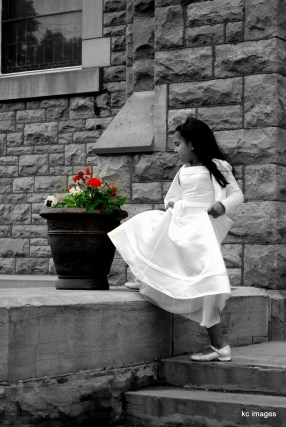 girl in white dress outside a church looking at red flowers