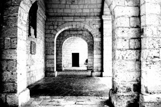 a colourless photo of three stone arches. there is a black rectangular door past them