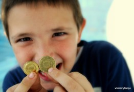 close up of little boy gleefully holding coins in front of his face
