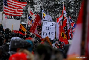 "the view over a crowd of people looking at a sign that says ""Idle no more"". large snow flakes are everywhere. many people are holding signs."