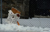 a sign left in the snow against a chain link fence with a grey stone building in the background