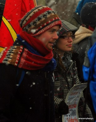 a man in a toque and a scarf next to a woman with a sign in her hand.