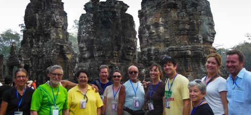 Most of our biking group stayed on for the post-trip into Cambodia. Can you see the faces in the wall of the temple above our group?
