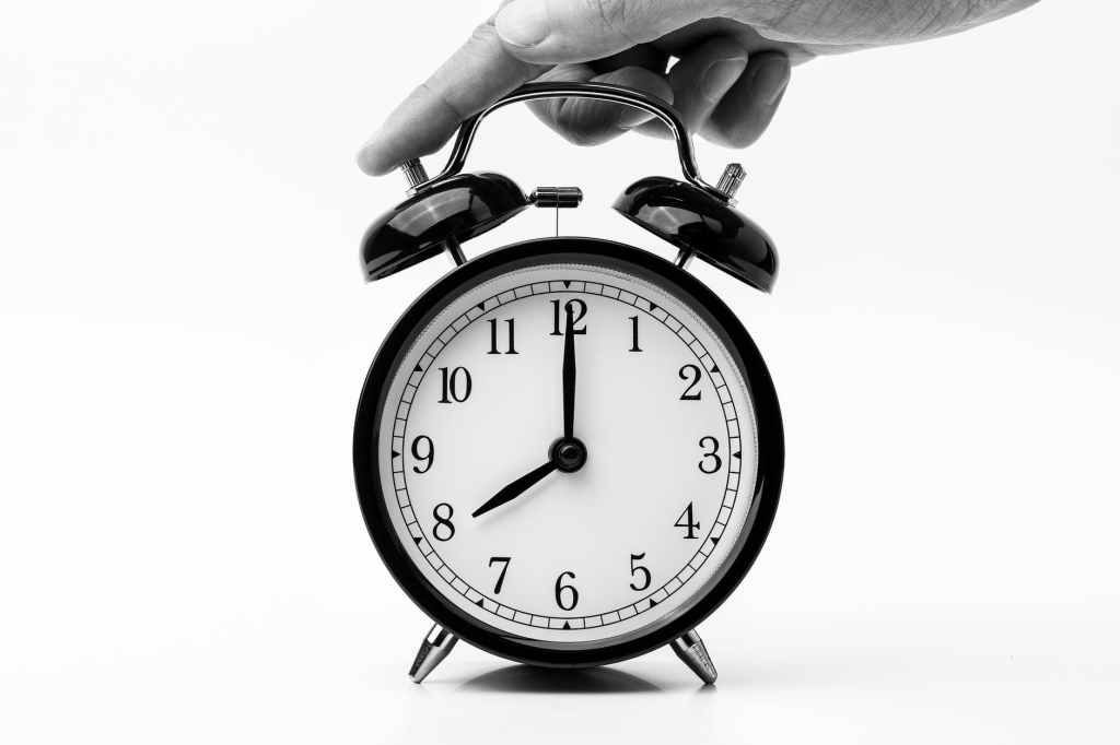 person touching black two bell alarm clock