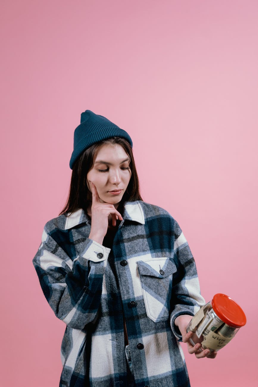 woman in blue plaid shirt holding a glass jar of money looking pensive