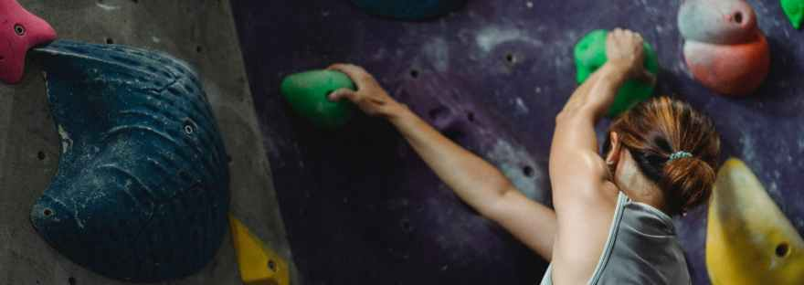 woman grabbing grips while ascending on climbing wall