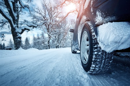 car with snowy tires on a snow covered ground near snow covered trees