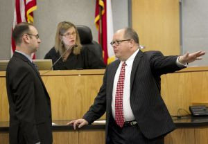Former prosecutor Steve Brand, left, and defense lawyer Jon Evans, right, confer at the bench with Judge Julie Kocurek in the capital murder trial of Darius Lovings.