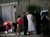De quoi parle le curé en soutane (sur la droite de la photo) avec ses fidèles?