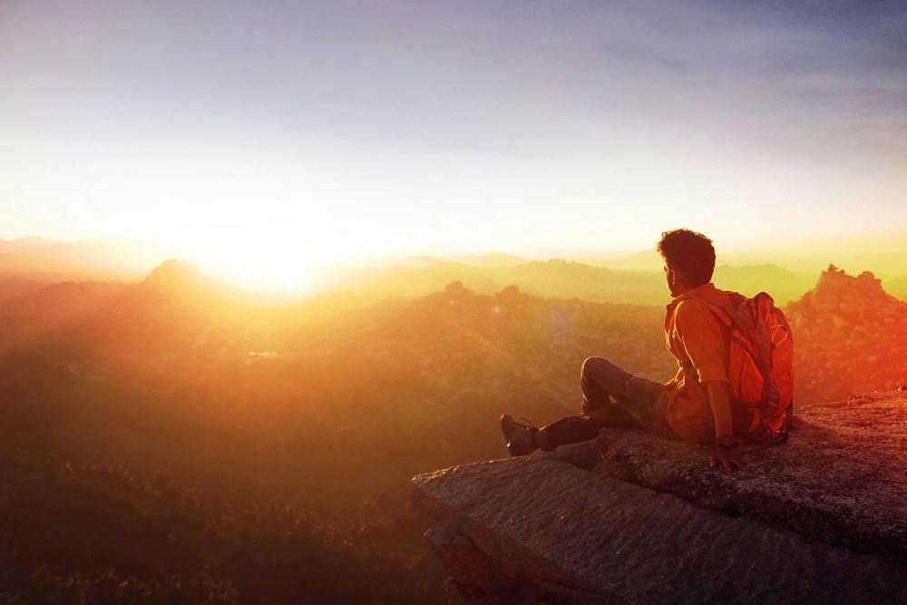 Homme assis sur une montagne face à un coucher de soleil. Cette image représente une pensée du jour écrite par Christiane Singer.