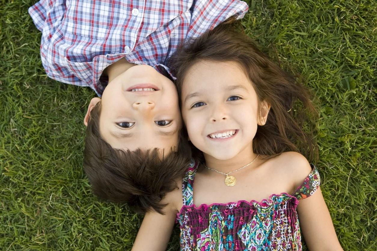 Un garçon et une fille regardant le ciel en souriant allongés dans l'herbe. Module 6 : Amoureusement l'un et l'autre.