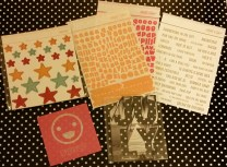 Clockwise from top left: Chipboard stars, vellum alphas, word stickers, JULY black and white chipboard photo, smiley lenticular card
