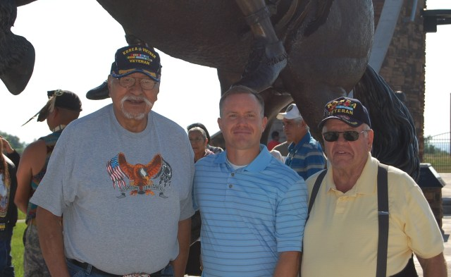 """Jerime Hooley (center) presents his 13-foot bronze statue """"Ute Warrior Chief"""" with Ute Tribal Elders Bob Chapoose (left) and Dolan Sorenson (right) at the unveiling ceremony held July 2, 2016 at the Fort Duchesne Ute Indian Tribe Veteran Memorial Park. Photo courtesy of MaKay Hooley"""