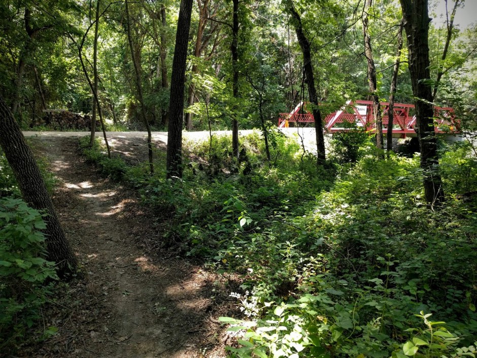 The Creekside Trail emerges onto the Backbone near the Sinclair-Hegwald Bridge. A right turn will lead you to the Western Trailhead (and the Southwind Rail Trail beyond), while a left will lead you back to the east, with additional singletrack opportunities.