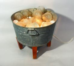 Bucket of Light – 17 x 18 x 3 Wash tub with burnt out light bulbs and string of Christmas lights. Kathy used lightbulbs in several pieces. She cast them in concrete and made them out of latex rubber as well.