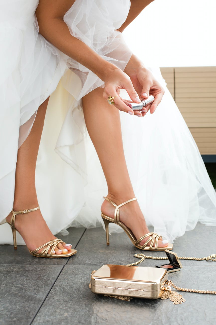 crop bride with makeup tools before wedding ceremony
