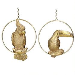 Gold Christmas decorations with hanging parrot and toucans against white background