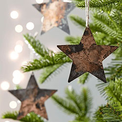 Copper star shaped decorations hanging on Christmas tree branches