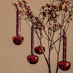 Red Christmas bell decorations hanging on branch