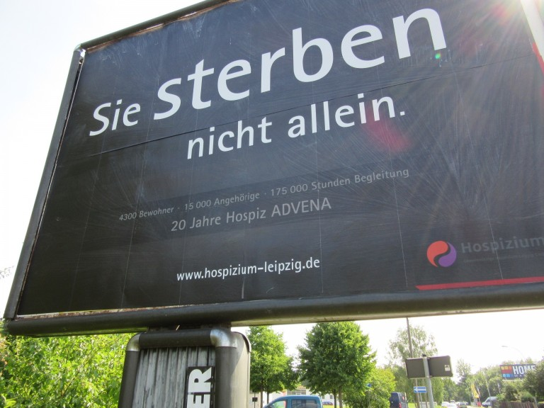 A billboard currently displayed in Leipzig-Engelsdorf, reading: You DIE – not alone. What sounds like an advertisement for death itself is one for a Leipzig hospice. (Photo: Maximilian Georg)