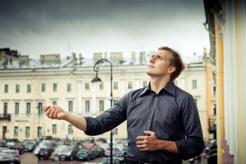 Conductor Vasily Petrenko outside with baton